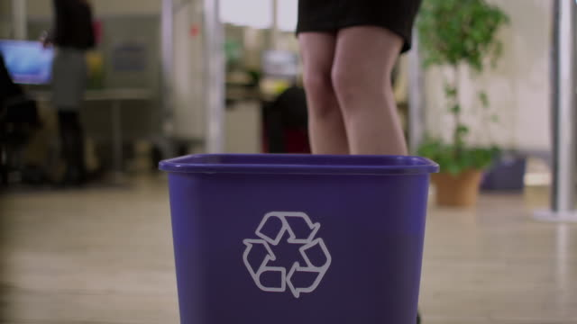 CU MS TD SELECTIVE FOCUS Woman throwing out papers into recycling basket in office, Appleton, Wisconsin, USA