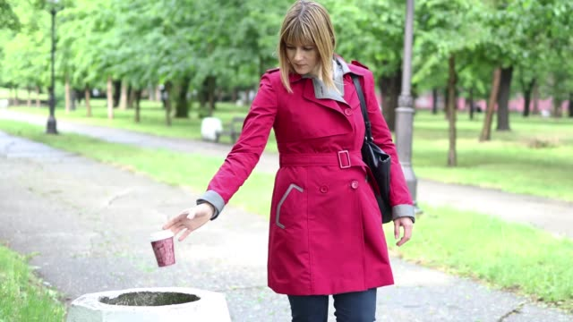 woman throwing paper cup in trash can - coffee cup stock videos & royalty-free footage