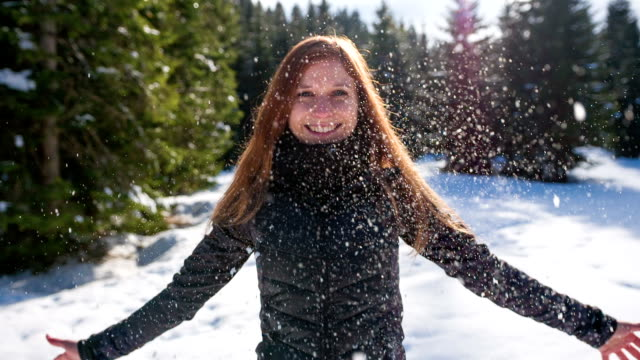 Woman throwing snow in the air