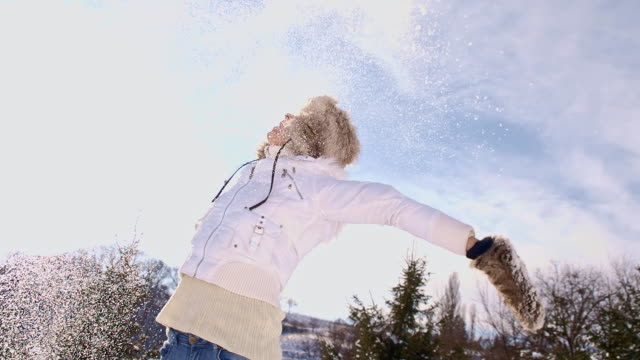 SLO MO Woman Throwing Snow Up In The Air