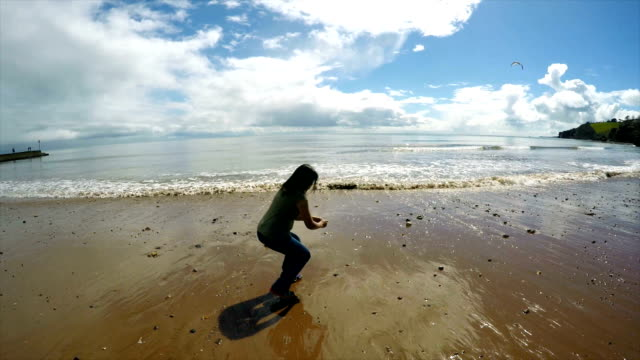 woman throwing stones into sea - devon stock videos & royalty-free footage