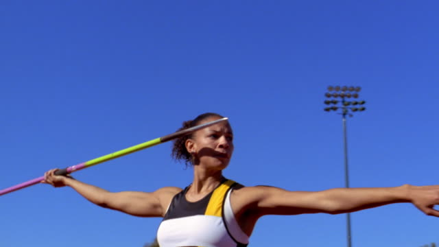 A woman throws a javelin.