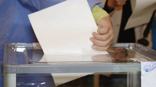 stockvideo's en b-roll-footage met woman throws election ballot - stembus
