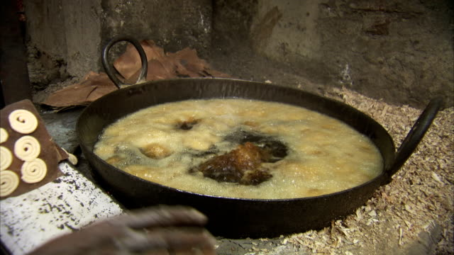 A woman throws food into a boiling pot in India.