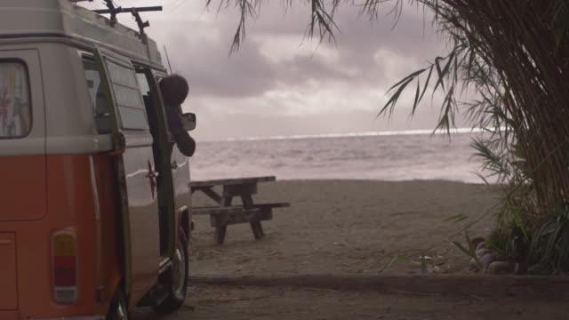 woman throws frisbee to man in van by beach, slow motion - lieferwagen stock-videos und b-roll-filmmaterial