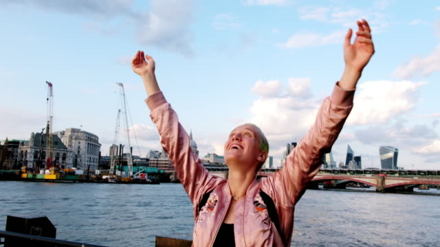 woman throws her hands up in the air excited to be in london along the thames river. - naga river stock videos and b-roll footage