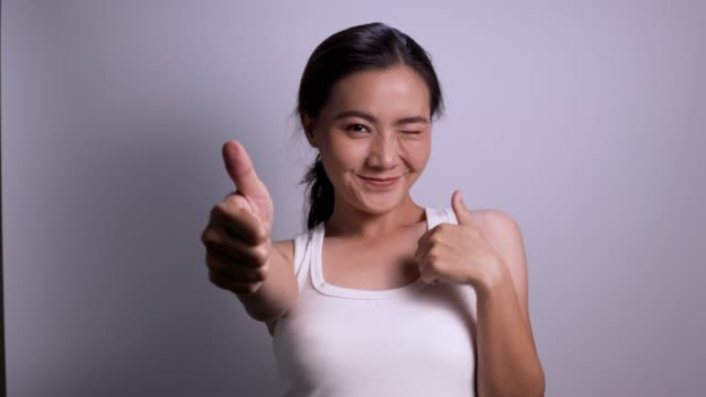 woman thumb up look at camera isolated white background 4k - model object stock videos & royalty-free footage