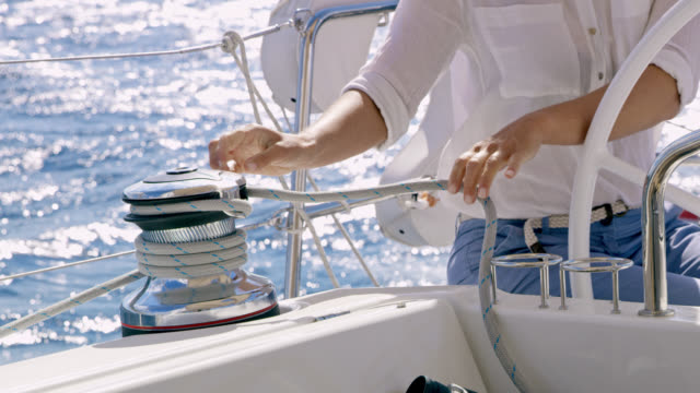 ZI Woman tied a rope around a winch while navigating a sailboat