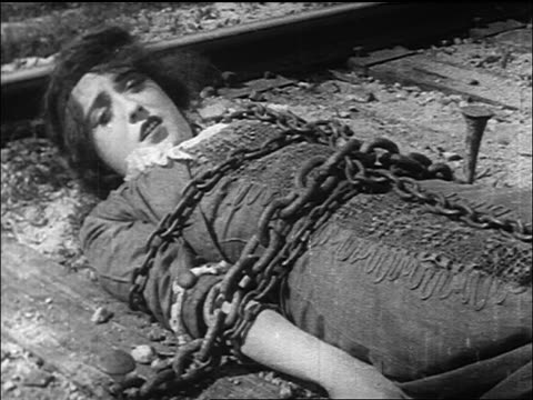 vídeos y material grabado en eventos de stock de b/w 1913 woman (mabel normand) tied to railroad tracks with chains calling for help - tramway