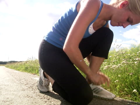 a woman tieing her shoes during a jogging tour next to a corn field sweden. - joggerin stock-videos und b-roll-filmmaterial