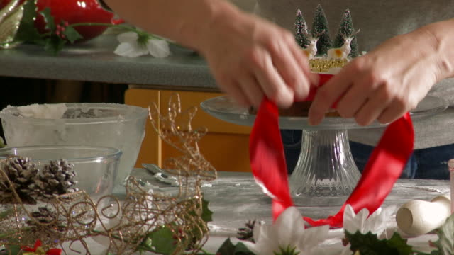 Woman Ties a Red Ribbon Around A Decorated Christmas Fruit Cake