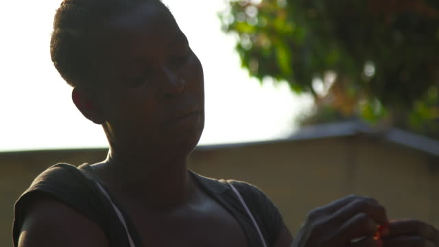 woman ties disabled girls hair in angola - treccine video stock e b–roll