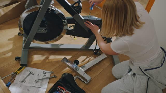 vídeos de stock, filmes e b-roll de ms mulher apertando um parafuso enquanto monta a bicicleta de exercício em casa - establishing shot
