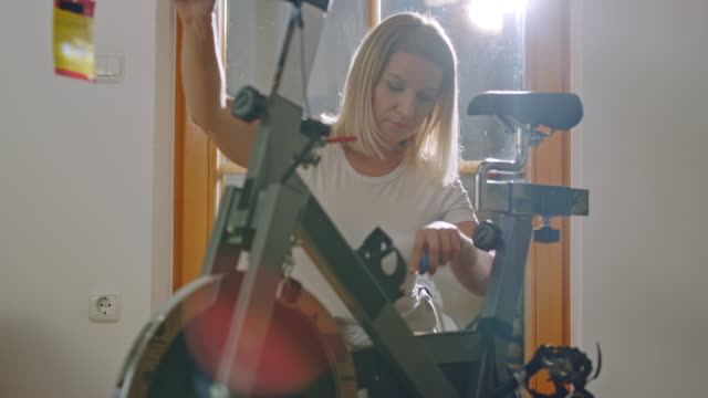 ds woman tightening a screw while assembling the exercise bike at home - adjusting stock videos & royalty-free footage