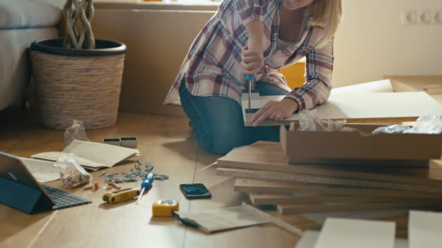 slo mo woman tightening screws while assembling the furniture - furniture stock videos & royalty-free footage