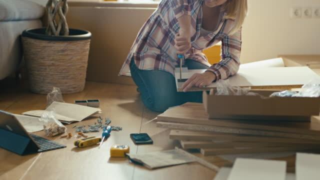 vídeos de stock e filmes b-roll de slo mo woman tightening screws while assembling the furniture - prateleira mobília