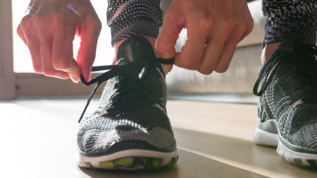 vídeos de stock e filmes b-roll de woman tightening the knot on her sports shoe, getting ready for morning run - preparação