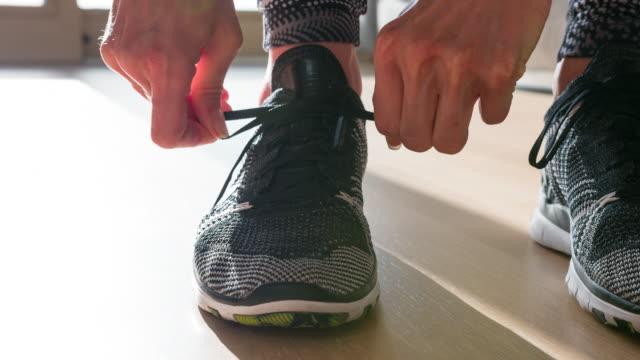 woman tightening the knot on her sports shoe, getting ready for morning run - alla moda video stock e b–roll