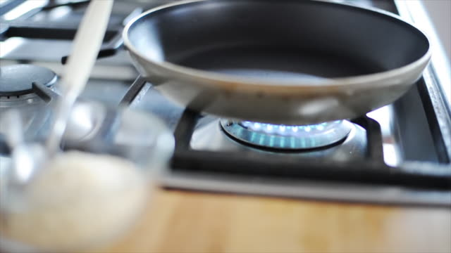 Woman toasting chopping nuts on gas stove
