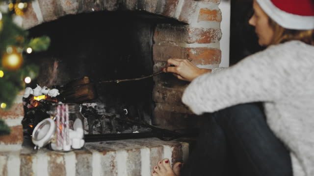 4K Woman toasting marshmallows over flames in fireplace, real time
