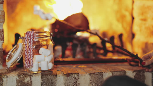 4k woman toasting marshmallows over flames in fireplace, real time - candy cane stock videos & royalty-free footage