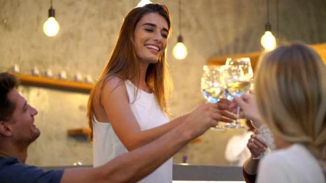 Woman Toasting Wine Glasses With Friends In Bar