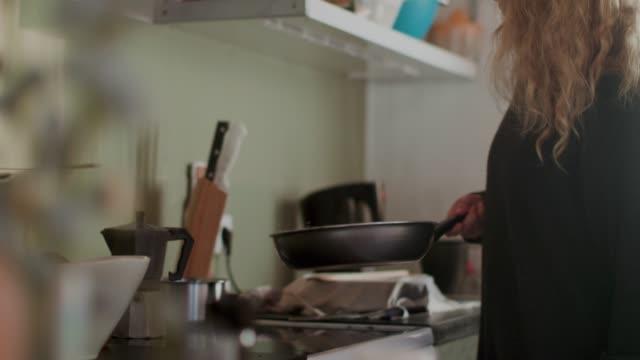 vídeos y material grabado en eventos de stock de woman tossing granola in frying pan - cocina