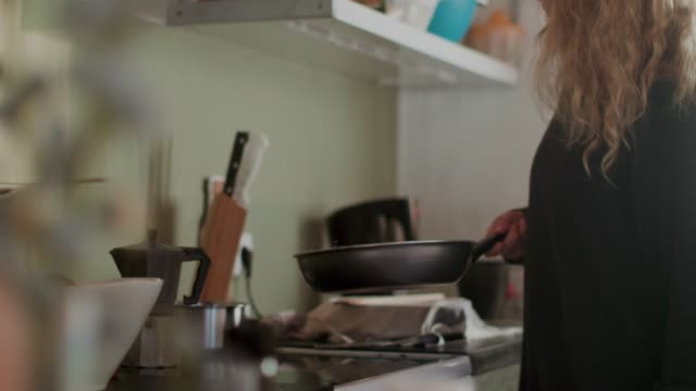 vídeos de stock e filmes b-roll de woman tossing granola in frying pan - kitchen
