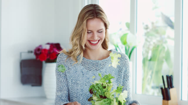 a woman tossing salad leaves in a colander - salad stock videos & royalty-free footage
