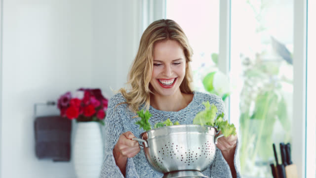 A woman tossing salad leaves in a colander