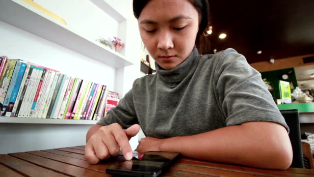 Woman touch a Smart phone for business in cafe