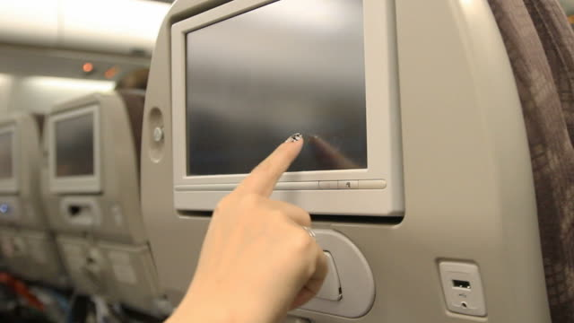 Woman touch airplane monitor