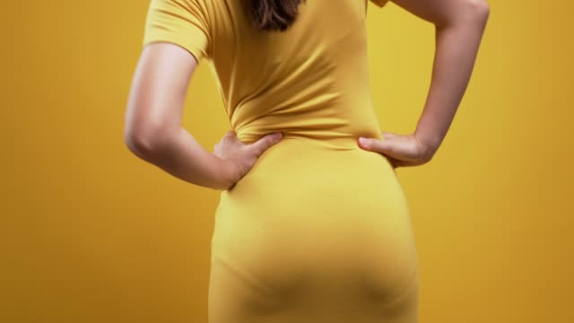 vídeos de stock e filmes b-roll de woman touching back pain over isolated yellow background - meninas adolescentes