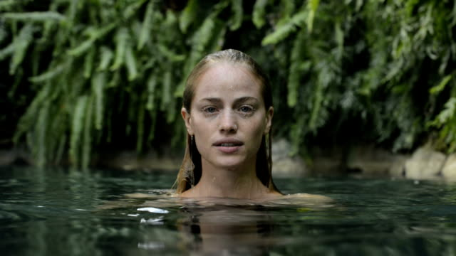Woman touching her face in a natural pool