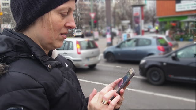 vídeos y material grabado en eventos de stock de woman touching her smart phone at the street. there is a lot of traffic.its christmas time in germany, europe. - chaqueta de esquiar