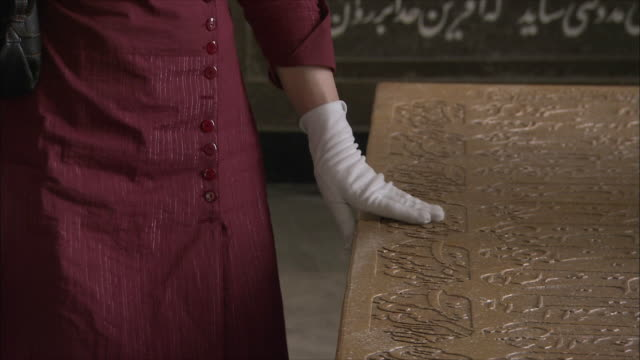 cu woman touching tombstone at tomb of poet saadi, shiraz, iran - formal glove stock videos and b-roll footage
