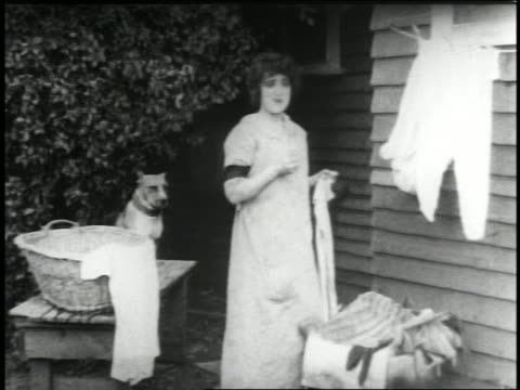 B/W 1915 woman (Mabel Normand) touching underwear on clothesline + talking to someone offscreen