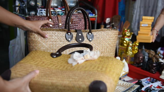 woman tourist choosing a handmade bag at souvenir shop in thailand. - souvenir stock videos and b-roll footage