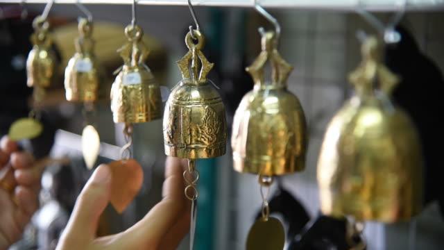 vídeos de stock e filmes b-roll de woman tourist choosing the bells at souvenir shop in thailand. - sino