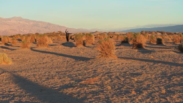 vídeos de stock, filmes e b-roll de uma mulher, turista, explorando o campo de milho do diabo no vale da morte, califórnia, no nascer do sol no inverno. - usa