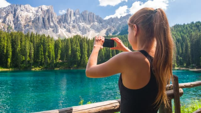woman tourist exploring dolomites mountainside, standing by lake carezza in trentino with latemar mountain range in background, taking pictures with smartphone - dolomites stock videos & royalty-free footage