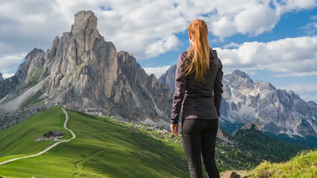 woman tourist exploring italian mountainside, hiking and admiring the view of giau mountain pass, dolomites - high up stock videos & royalty-free footage