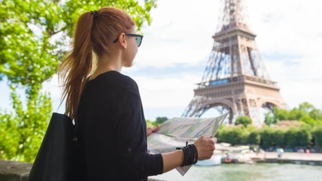 frau touristische erkundung von paris mit karte, blick auf eiffelturm aus über den fluss seine - hoch position stock-videos und b-roll-filmmaterial