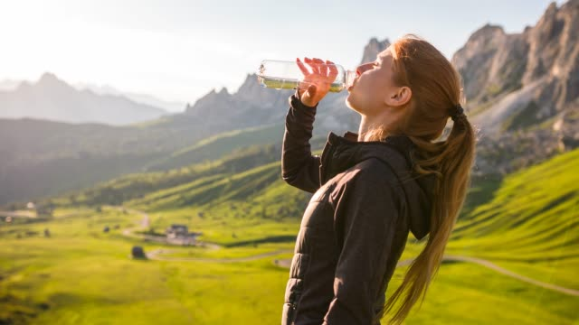 woman tourist in mountainside illuminated by the sun, hydrating with water - reusable stock videos & royalty-free footage