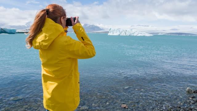 Frau Tourist auf Islands Diamond Beach, Breidamerkursandur, schwebte fotografieren Eisberge von Gletscherlagune Jökulsárlón