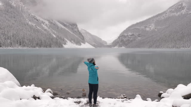 woman tourist outstretched hand in lake louise - admiration stock videos & royalty-free footage