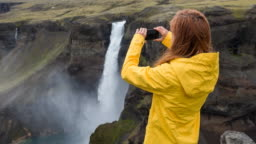 Woman tourist photographing Iceland's natural landmarks