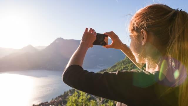 Touristenanreiterin fotografiert Panoramablick auf den italienischen Comer See mit Smartphone