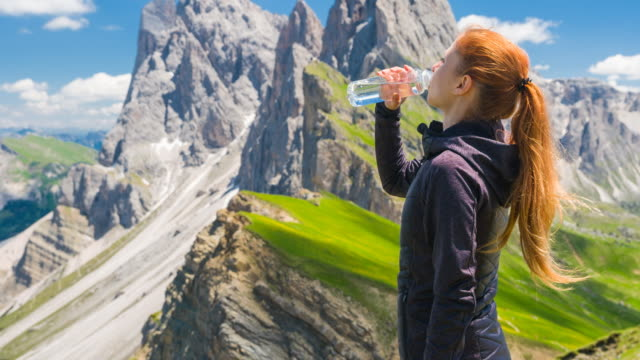 woman tourist resting from hiking in mountains, drinking from a water bottle - thirsty stock videos & royalty-free footage