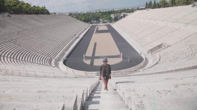 a woman tourist sightseeing at the panathenaic stadium in athens, greece. - athens greece stock videos & royalty-free footage
